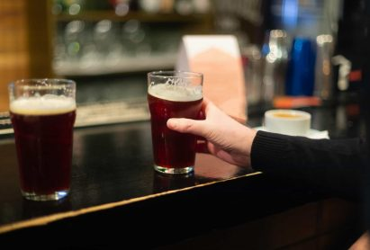 Beer glasses with dark beer are on the bar counter