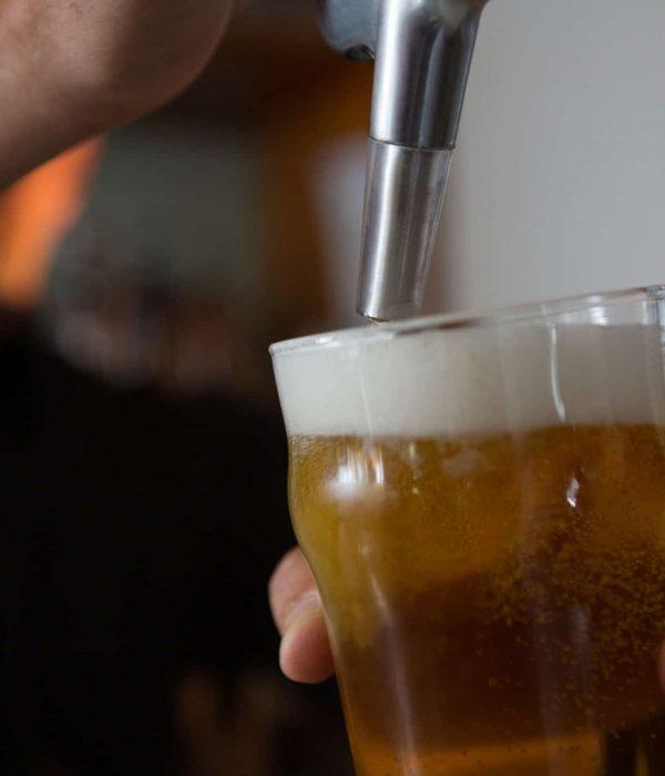 Brewer filling beer in beer glass from beer pump in bar